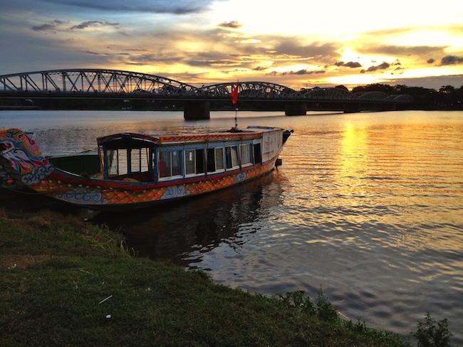 Puesta de sol en Hué, ante una de las barcas que pasea a los turistas por el Río de los Perfumes