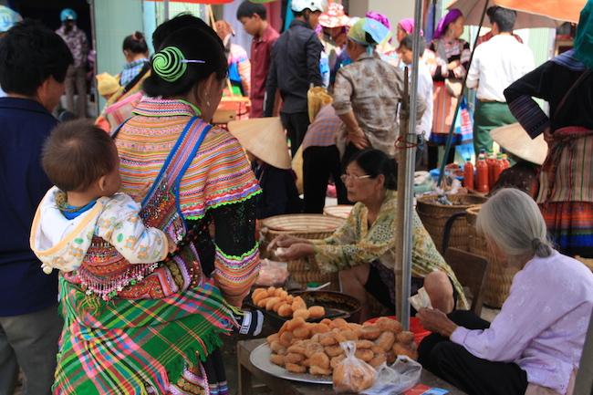 Esta madre demuestra que la riqueza de colores de los vestidos hmong flor incluyen los complementos para llevar a su hijo