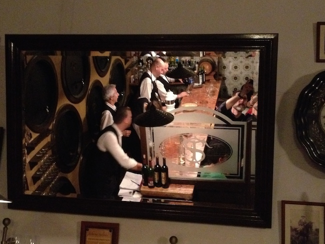 La mñitica y antigua barra de la Taberna Salinas vista en un espejo de la sala: el editor de crónicas viajeras se esconde en la foto...